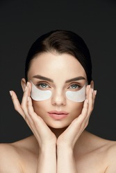 Under Eye Treatment. Woman Face With Patches Under Eyes. Beautiful Young Female With Fresh Soft Skin Applying Beauty Patches Under Eyes On Black Background. High Resolution