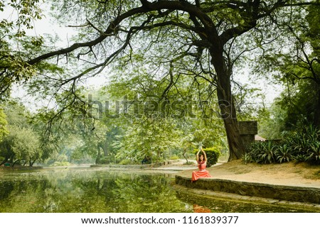 Under large tree a girl sits and studies yoga in the lotus poses. Hands raised up. Near the lake with a beautiful reflection of the tree. Gardens of Lodi, India. Advertising of yoga tours. Meditate.