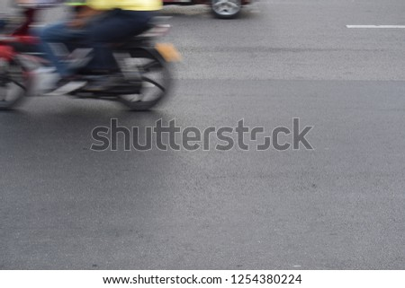 under shot of speed motion of the motorcycle was running pass the road with two people riding on it. #1254380224