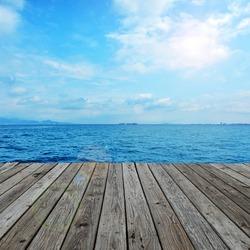 Under the blue sky, wood platform beside the sea.