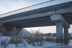 under the bridge in winter evening, concrete pillars, metal railing, dry river reeds, water covered with ice and snow, white cold agricultural field in distance, sky with some clouds