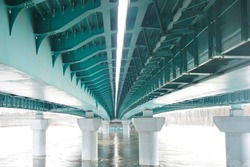 Under the bridge river. New reinforced concrete and iron road bridge. Bottom view. Background. river under ice. winter season.