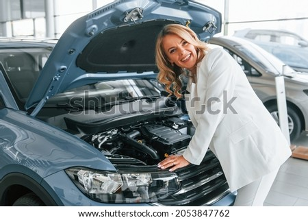 Under the car hood. Woman in formal clothes is indoors in the autosalon.