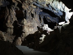 Under the ground. Beautiful view of the stalactites and stalagmites in the underground cave. Speleology, the concept of active recreation, extreme travel.