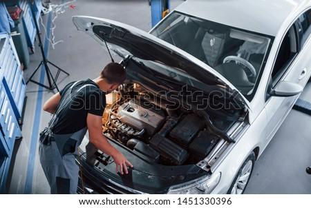 Under the hood. Man in grey uniform repairs white automobile indoors.