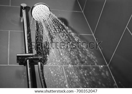 Under the shower jet/Image taken from below of a shower spraying water jets inside a bathroom bathtub.