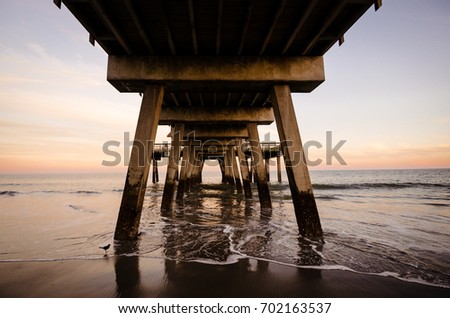 Stock Photo Under the Tybee Island pier in Southern Georgia United States at sunset on the Atlantic Ocean