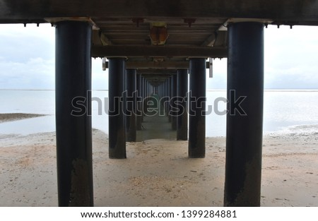 Under Urangan pier perspective view. Under a pier in Hervey Bay (Queensland, Australia), showing the structure of the pilings and support structure. #1399284881