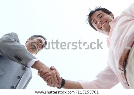Under view of two businessmen shaking hands against the sky, smiling.