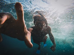 Under water shot using a gopro while snorkeling in action splashing water reaching hand diving swimming during holidays vacation adventure movement of a person in the ocean sea pool.