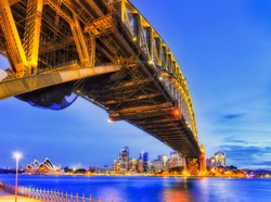 Underbelly of steel arch of the Sydney harbour bridge across harbour at sunset to city CBD.