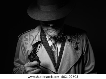 Undercover agent holding a pistol in the dark, 1950s noir film character #603107603