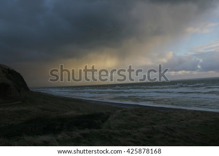 Underexposed picture of an incoming storm on the coast of New Zealand.The underexposure is a key element to the picture because it shows the threat of the storm and giving a painting-like effect.