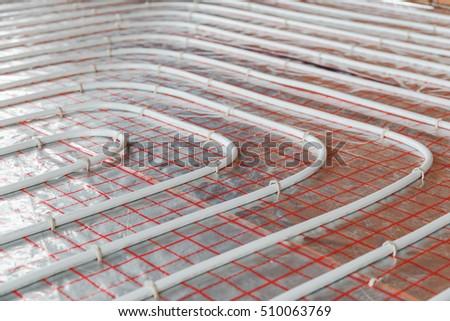 Underfloor heating installation. Close up on water floor heating system interior. plumbing pipes. Individual Heating. #510063769