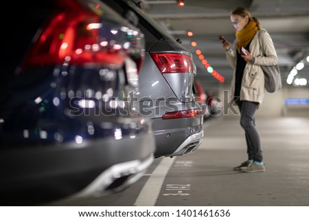 Underground garage or modern car parking with lots of vehicles, perspective of the row of the cars with a female driver looking for her vehicle
