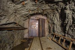 Underground gold mine shaft tunnel drift with rails and door