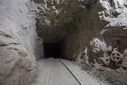 Underground gold mine shaft tunnel drift with rails and light