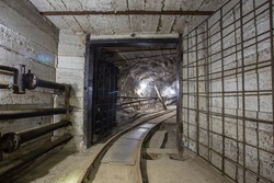 Underground gold ore mine tunnel with rails and water door