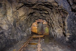 Underground old abandoned iron mine tunnel with rusty door