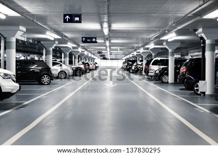 Shutterstock Underground parking with cars. White colors.