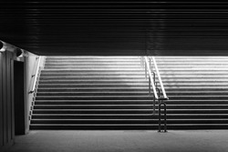 Underground passage walk. Exit to the city. Way out. Abstract black-and-white architecture photograph with back light.