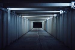 Underground pedestrian crossing. A long concrete tunnel with lanterns in the city underground. Underpass. underground passage