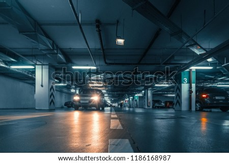 Underground public garage parking with cars, movie style toned