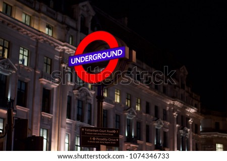 Underground sign on Oxford Street above a sign with walking distances to Tottenham Court Road and Piccadilly Circus.