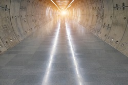 Underground tunnel.Transport walkway by Tunnel Boring Machine for infrastructure subway with raw concrete segments wall.Light at the end of the tunnel.