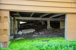 Underneath a house cabin structure foundation cinder block crawl space support system architecture wood construction carpenter