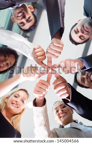 underneath view multicultural co-workers with thumbs joined together