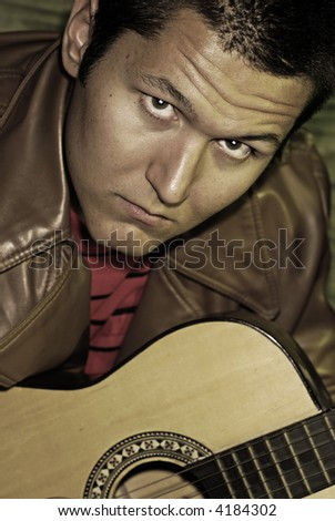 Undersaturated portrait of a young guy with a guitar