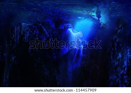 Undersea fantasy scene with a mysterious creature looking into the glowing light created with digital art.