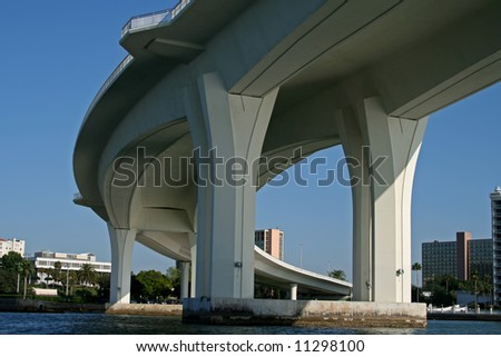 underside of curved concrete bridge support against blue sky