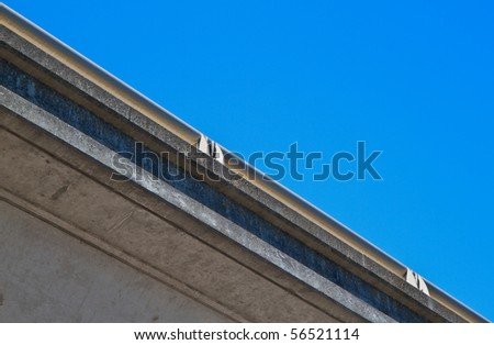 Underside of freeway concrete and steel railing against blue cloudless sky