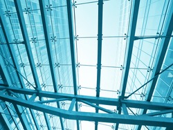 underside wide angled and perspective view to steel blue glass airport ceiling through high rise building skyscrapers, business concept of successful industrial architecture