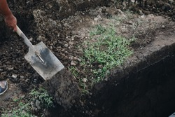 Undertaker shovels the soil to cover the grave and bury the dead.  Selective focus. Copy space.