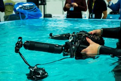Underwater camera. Diver holds a camera for filming underwater