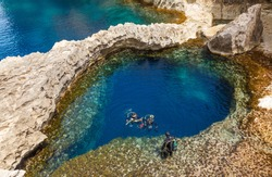 underwater cave in the form of heart and divers at Azure Window in Gozo, Malta