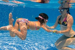 Underwater family in swimming pool. Mother teaching her child