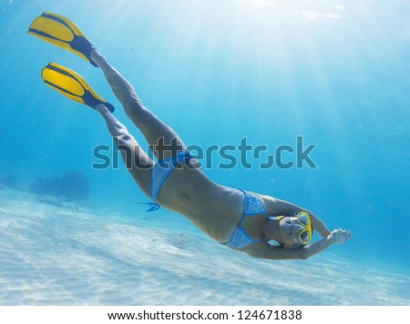 Underwater full length portrait of a woman snorkeling in tropical sea over sandy bottom