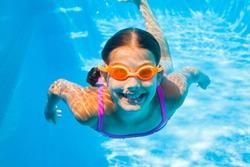 Underwater happy cute girl in swimming pool