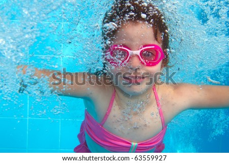 stock photo : underwater little girl pink bikini goggles blue swimming pool