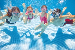 underwater photo of young family with kids in swimming  pool