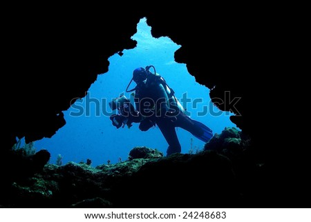 Underwater photographer entering cave system