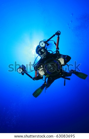Underwater Photographer with digital SLR camera in a housing scuba dives on a coral reef