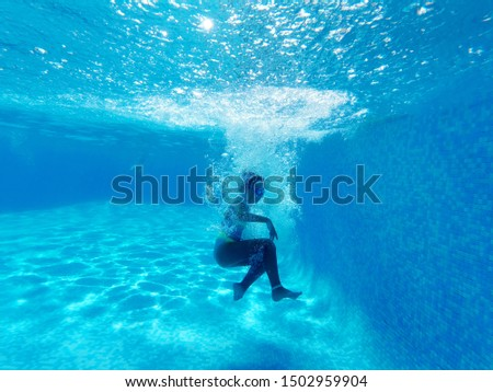 Underwater photography, small girl surrounded by bubbles wearing watersport goggles and swimwear falling in blue water of swimming pool, copy space for your ad text, active healthy lifestyle concept #1502959904