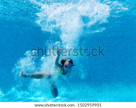 Underwater photography, small girl surrounded by bubbles wearing watersport goggles swimwear falls in blue swimming pool water copy space for your ad text, summer holidays activity, healthy lifestyle #1502959901