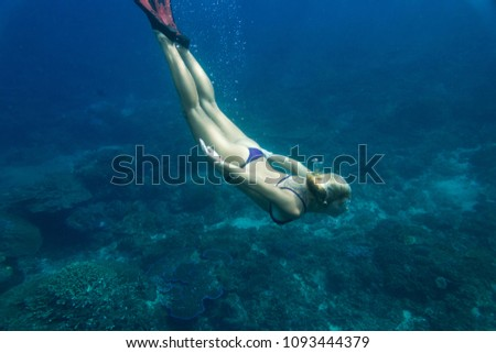 underwater pic of young woman in bikini and fins diving in ocean alone