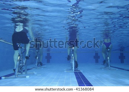 Underwater picture of people practicing spinning - aquabike.